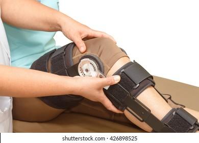 Orthopedist secures leg brace on knee, knee brace support for leg or knee injury