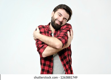 ortrait confident smiling man hugging himself. I am the best concept. Soft clothes after washing
