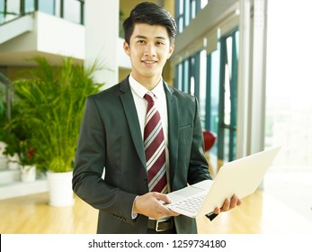 ortrait of a young asian business man, holding laptop computer, looking at camera smiling