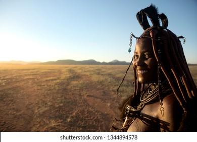 Orupembe, Kunene Region, Namibia. - May 13, 2018 : A young Himba woman herds her cattle home after a days grazing. The Himba still live a traditional nomadic life in the Kunene Region of Namibia.