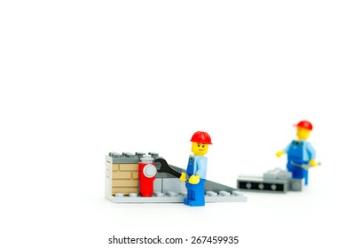 Orvieto, Italy - April 5th 2015: Lego mini figure workman at work on white background. Road Works. Lego is a popular line of construction toys manufactured by the Lego Group