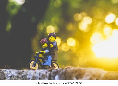 Orvieto, Italy - August 16th 2015: Couple of friends Lego minifigure on bicycle in a sunset
