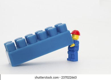 Orvieto, Italy - December 10th 2014: Lego mini figure workman at work on white background . Lego is a popular line of construction toys manufactured by the Lego Group