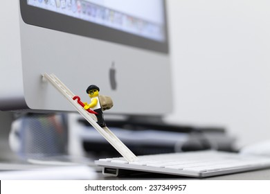 Orvieto, Italy - December 13th 2014: Lego mini figure thief on apple computer. Lego is a popular line of construction toys manufactured by the Lego Group