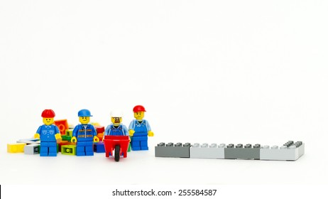 Orvieto, Italy - February 14th 2015: group of workman Lego mini figure build a wall. Lego is a popular line of construction toys manufactured by the Lego Group