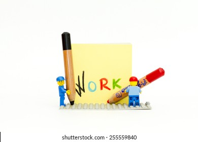 Orvieto, Italy - February 22th 2015: Lego men write in a notebook the word work. Lego is a popular line of construction toys manufactured by the Lego Group
