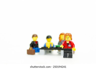 Orvieto, Italy - February 5th 2015: Lego business woman with her staff, people group in background. Lego is a popular line of construction toys manufactured by the Lego Group