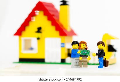 Orvieto, Italy - January 16th 2015: couple of young guys Lego mini figure  buy a house. Lego is a popular line of construction toys manufactured by the Lego Group