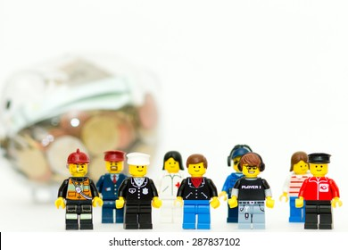 Orvieto, Italy - June 16th 2015: Group of Lego mini figures near a piggy bank. Save a money.  Lego is a popular line of construction toys manufactured by the Lego Group