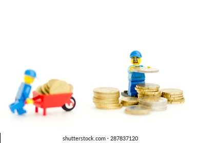 Orvieto, Italy - June 16th 2015: Lego workman mini figure building a tower with coins. Save a money. Lego is a popular line of construction toys manufactured by the Lego Group