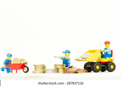 Orvieto, Italy - June 16th 2015: Lego workman mini figure building a tower with coins.Save a money.  Lego is a popular line of construction toys manufactured by the Lego Group