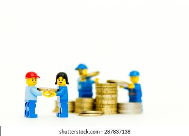 Orvieto, Italy - June 16th 2015: Group of Lego mini figure building a tower of coins. Save a money. Lego is a popular line of construction toys manufactured by the Lego Group