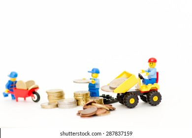 Orvieto, Italy - June 16th 2015: Group of Lego workman playing with coins. Save a money.  Lego is a popular line of construction toys manufactured by the Lego Group
