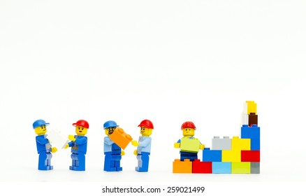 Orvieto, Italy - March 8th 2015: group of workman Lego mini figure build a wall. Lego is a popular line of construction toys manufactured by the Lego Group