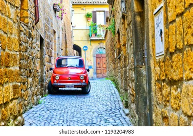 Orvieto, Italy - September 13, 2016 : View of a small red car in the historic cityscape in Orvieto on September 13, 2016.