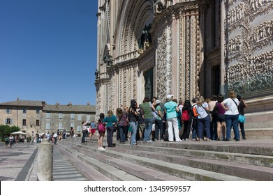 ORVIETO, ITALY - SEPTEMBER 14 2013 - Tourists stand on the steps in front of the cathedral, get an explanation of the relief on the walls and wait until they can enter the Duomo Cathedral