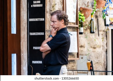 Orvieto, Italy - September 3, 2018: Italian restaurant cafe outdoor sign by street in Umbria with manager owner chef looking at menu in historic city town village