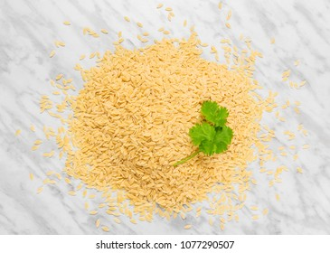 Orzo pasta with green coriander leaves, on marble background. Rice-shaped tiny pasta.