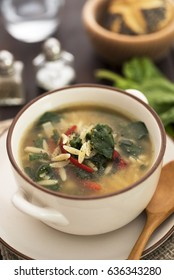 Orzo soup with vegetables on wood table