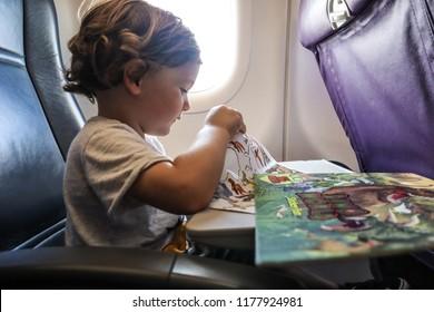 Osaka Airport, Osaka / Japan - 08 09 2018: Kid playing with a stickers book on a plane seat