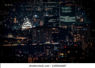 Osaka Castle illuminated at night in birdeye or top view with cityscape and high building around, Osaka Prefecture, Japan.