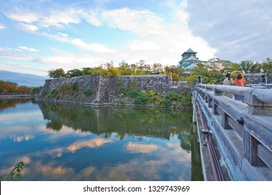 Osaka Castle is the most famous castle in Japan. The castle is open to the public and it is a main tourist attraction in Osaka, Japan. Some people are at the observation deck in Osaka Castle.