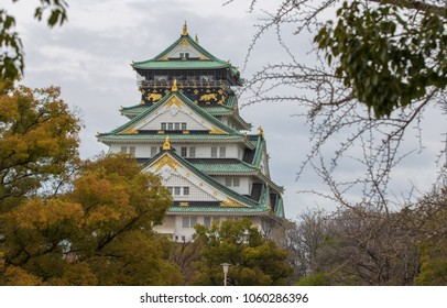 Osaka castle in a spring day under fully cloudy sky in front of sylvan shady trees