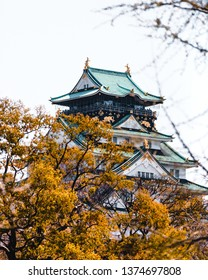 Osaka Castle surrounded with trees and cherry blossoms in Japan