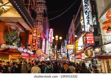 OSAKA, JAPAN - 13TH JANUARY 2019: A view along streets in the Dotombori area of Osaka at night. Neon lights, shops, restaurants and lots of people can be seen.