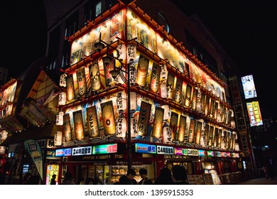 OSAKA, JAPAN - 13TH JANUARY 2019: Colourful architecture in the Shinsekai  neighbourhood of Osaka at night. Lots of people can be seen.