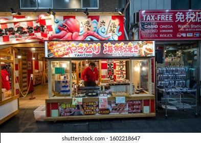 Osaka, Japan- 28 Nov, 2019: Small street seafood restaurant with chef cooking Yakitori on stove for customers in Kuromon market.