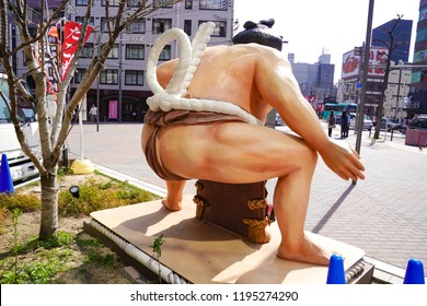 Osaka, Japan - 4 Mar 2018 - Sumo Statue beside the traditional Japan food truck. the table and chair are around the area and settle on the footpart in Osaka, Japan.