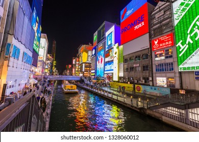 Osaka, Japan - April 1, 2017: Tourist boat cruise pass Dotonburi district which is known for shopping street, entertainment, food and Gulico running man sign.
