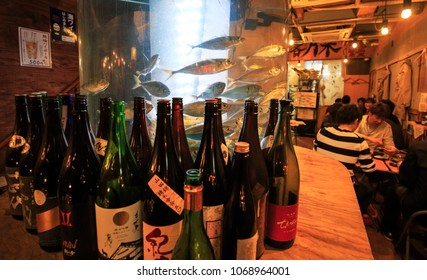 Osaka, Japan - April 14, 2018: Sake bottles and fresh fish entice customers at the entrance of a popular local restaurant