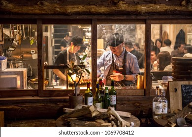 Osaka, Japan - April 14, 2018: Restaurant workers prepare stick food in the window of a full restaurant