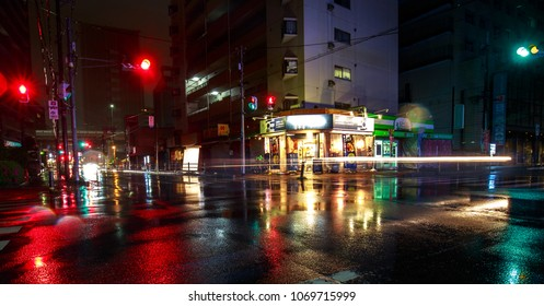 Osaka, Japan - April 14, 2018: Car lights on a quiet street in heavy rain