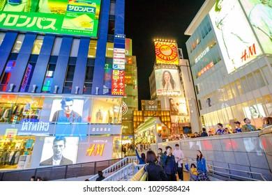 Osaka, Japan - April 29, 2017: people on Ebisu Bridge in front of entrance to Ebisu Bashi-Suji Shopping Street in Namba District, one of the main tourist destinations in Osaka. Cityscape by night.
