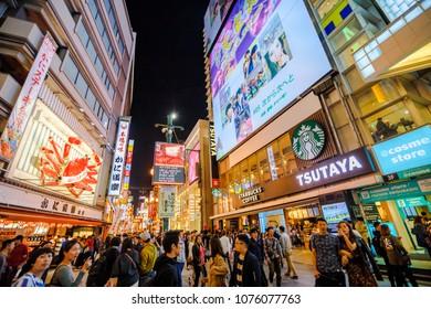 Osaka, Japan - April 29, 2017: crowd of people for Golden Week in Dotonbori area with Kani Doraku crab sign of popular Japanese restaurant. Namba District, nightlife scene.