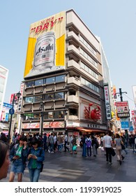OSAKA, JAPAN - APRIL 3, 2018: Wide vertical view of the iconic Asahi Super Dry beer billboard at Dotonbori square, Namba district, on a clear, sunny day. Travel and tourism.
