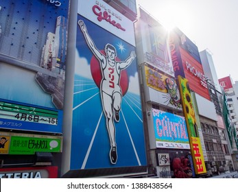 OSAKA, JAPAN - APRIL 3, 2018: Wide angle view of the famous Glico running man sign at Ebisu Bridge on a sunny afternoon. Dotonbori, Chuo. Travel and tourism.