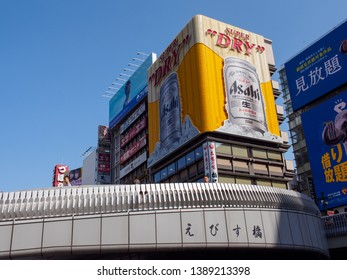 OSAKA, JAPAN - APRIL 3, 2018: Wide vertical view of the iconic Asahi Super Dry beer billboard from Ebisu Bridge. Dotonbori, Namba, Chuo. Travel and tourism.