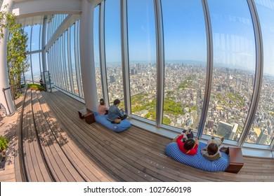 Osaka, Japan - April 30, 2017: tourists relax on the sofas inside the viewing platform of Osaka's Abeno Harukas, the tallest skyscraper in Japan, enjoying Osaka skyline