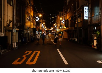Osaka, Japan - August 05, 2014 : Late Night Street view, people are walking in the middle of the road towards the incoming car.