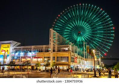 OSAKA, JAPAN - AUGUST 14, 2016: Night view of Japanese locals and tourists walking around Tempozan Harbor Village, where the Tempozan Giant Ferris Wheel is located next to Osaka Aquarium Kaiyukan.