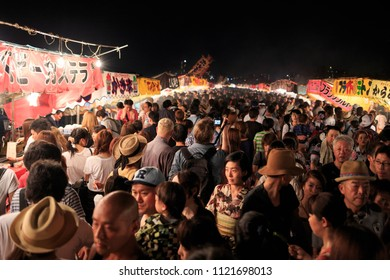 Osaka, Japan - August, 8 2015: Crowds of people walk by colorful food stalls at the Yodogawa Fireworks Festival