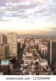 Osaka, Japan - Circa November 2015: Cloudy sky during sunset high above the city with mountains in background.