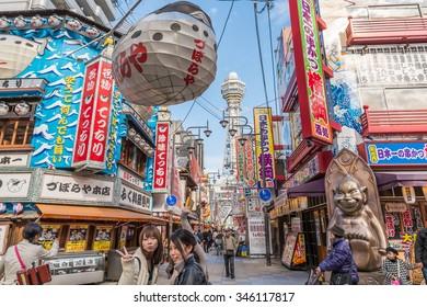 OSAKA, JAPAN - DECEMBER 1, 2015: Tsutenkaku Tower in Shinsekai (new world) district under clear blue sky daytime. Chinese Tourist people enjoy selfie, Puffer fish restaurant, bar, Kushikatsu, Kushiage