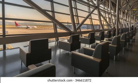 OSAKA, JAPAN - DECEMBER 1, 2015: Airport interior. Sofa Chair at Gate Executive VIP Lounge Waiting Area for airplane flight with Aircraft on runway at Golden Sky Sunset, Kansai International Airport
