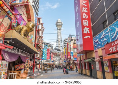 OSAKA, JAPAN - DECEMBER 1, 2015: Tsutenkaku Tower landmark of Osaka, Japan in Shinsekai (new world) under clear blue sky daytime. Tourist people visit Puffer fish restaurant, bar, Kushikatsu, Kushiage