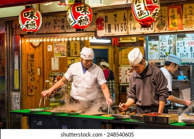 OSAKA, JAPAN - DECEMBER 27: Men cook traditional Japanese street food on December 27, 2014 in Osaka, Japan.